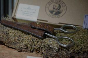 Mustaschtrimsax förpackad i brunt läderfodral. Liggandes på en träbit framför medföljande kartong i brunt.