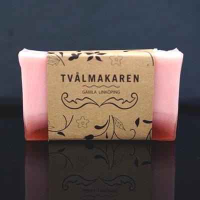 Ekologisk Handgjord tvål. Rektangulärgformad och inslagen i brunt papper med Tvålmakarens logga på. Rosa färg med röd botten, doft av Energi.