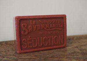 100 gram Rektangulärformad tvål från Frankrike. Tryckt text på framsidan. Mörk röd och rosa färg, doft av Seduction.