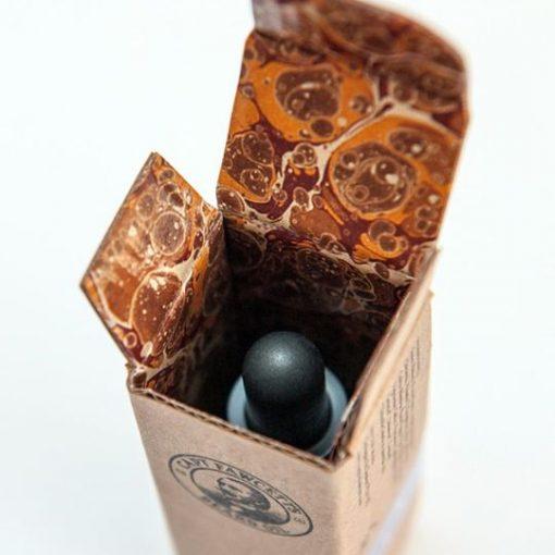 Captain Fawcett:s skäggolja ståendes i medföljande kartong. Förpackningen är öppen och visar det brun-oranga mönstret på insidan.