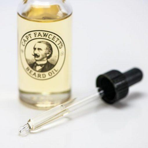 50 ml Kaptenes skäggolja. Glasflaska med svart gummipipett. Liggandes pippett med innehåll av oljan.