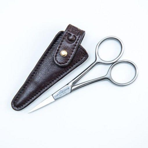 Mustaschtrimsax bredvid ett brunt läderfodral. Stängd sax.