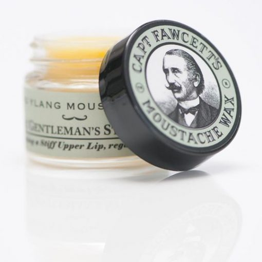 Mustaschvax i glasburk med gröna detaljer som symboliserar doften Ylang Ylang. Burken öppnad med locket halvt ståendes. Lock med målad bild av Kapten Fawcett.