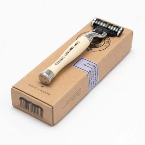Elfenbensfärgad rakhyvel med moderna Gillette blad. Ligger ovanpå tillhörande kartong.