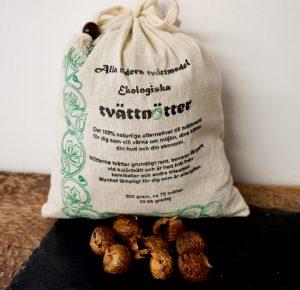 500 gram Ekologiska Tvättnötter i en vit tygpåse. Nedan för ligger bruna tvättnötter. Gröna detaljer målade på påsen med svart text. Påsen räcker till ungefär 75 tvättar och nötterna kan återanvändas. Tvättpåse för nötterna ingår.