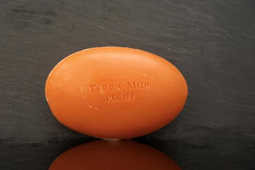 Tvål formad som gåsägg. Tryckt text på ovansidan. Röd färg, doft av persika.