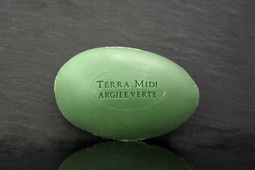 Tvål formad som gåsägg. Tryckt text på ovansidan. Mörkgrön färg, doft av oliv och grönlera.