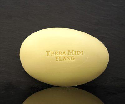 Tvål formad som gåsägg. Tryckt text på ovansidan. Ljusare gul eller beige färg, doft av Ylang.