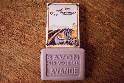 25 gram Rektangulärformad gästtvål från Frankrike. Lila av doften lavendel. Liggandes under medföljande kartong med motiv på: ett fat med dryck framför ett fält av lavendelblommor.