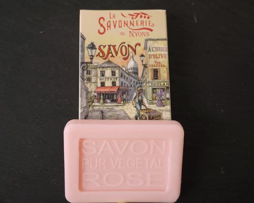 25 gram Rektangulärformad gästtvål från Frankrike. Ljusrosa av doften ros. Liggandes under medföljande kartong med motiv på: en animerad över en stad.