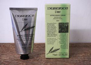 After shave från Durance L'ome. Doft av vetiver, gräs. Konformad produkt i metallfärgad yta med svart text. Skruvkork. Ståendes bredvid medföljande förpackning i ljusgrönt med svart text. Den ljusgröna färgen symboliserar den akutella doften, vetiver/gräs. 75 ml.