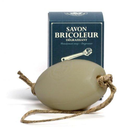 270 gram Handyman tvål. Vit ovalformad tvål liggandes framför medföljande kartong i mörkare blå färg med vit text. Tvålen har ett rep för att lätt kunna hänga upp den.